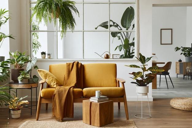 黄色いベルベットのソファ、植物、家具、本、木製の立方体、スタイリッシュなホームステージングのパーソナルアクセサリーを備えたスカンジナビアのオープンスペースのインテリアデザイン。テンプレート。