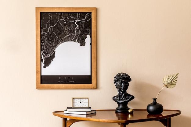 スタイリッシュな木製テーブル、金の時計、紙の花、本、エレガントなパーソナルアクセサリーを備えたリビングルームのインテリアデザイン。ベージュの壁に茶色の木製のモックアップポスターマップ。室内装飾。テンプレート。