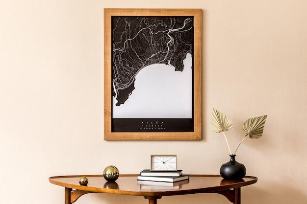 スタイリッシュな木製のテーブル、金の時計、紙の花、本、エレガントなパーソナルアクセサリーを備えたリビングルームのインテリアデザイン。ベージュの壁に茶色の木製のモックアップポスターマップ。室内装飾。テンプレート。