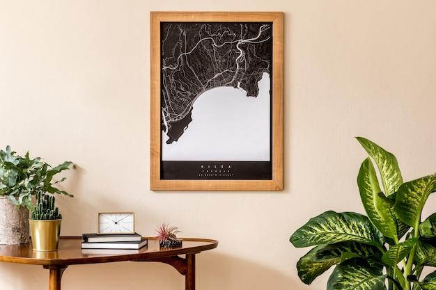 세련된 나무 테이블, 금 시계, 식물, 책이있는 거실의 인테리어 디자인. 베이지 색 벽에 갈색 나무지도입니다. 가정 장식 ..