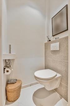 Дизайн интерьера небольшого современного туалета с белым туалетом в углу и картиной на стене