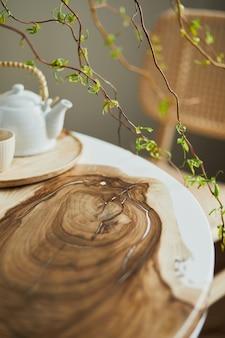 가족용 목재 및 에폭시 테이블, 등나무 의자, 꽃병에 꽃, 컵이 있는 찻주전자가 있는 세련된 식당 인테리어의 인테리어 디자인. 세부. 주형.