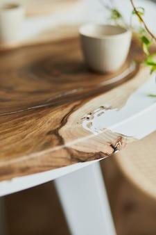 Дизайн интерьера стильной столовой с семейным деревянным и эпоксидным столом, стульями из ротанга, цветами в вазе и чайником с чашками. подробности. шаблон.