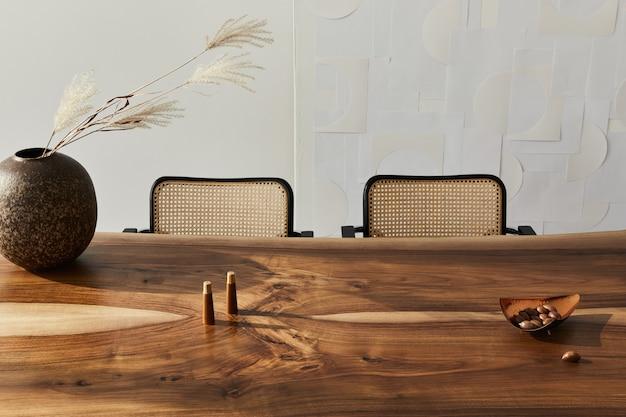 Дизайн интерьера стильного интерьера столовой с семейным деревянным столом, современными стульями, тарелкой с орехами, солонкой и перцем. абстрактные картины на стене. белая стена..