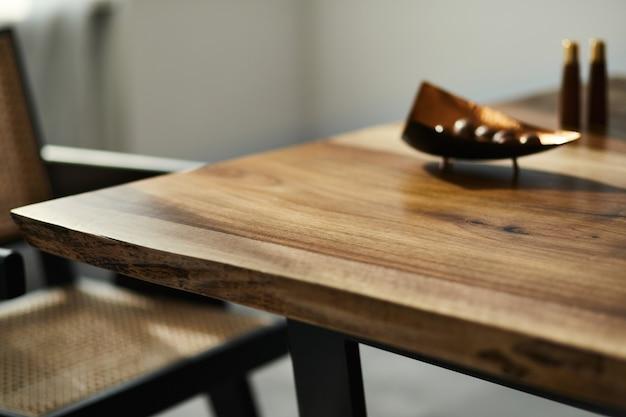 Дизайн интерьера стильной столовой с семейным деревянным столом, современными стульями, тарелкой с орехами, солонкой и перцем.