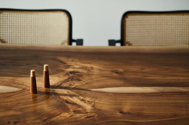 가족 용 나무 테이블, 현대적인 의자, 소금 및 후추 통이있는 세련된 식당 인테리어의 인테리어 디자인. 세부. 흰 벽.