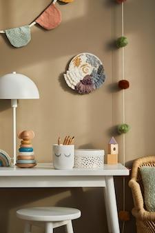 Дизайн интерьера стильной детской комнаты с белой полкой, деревянными игрушками, куклами, детскими аксессуарами, белой лампой, уютным декором и висящими хлопковыми флажками на бежевой стене. шаблон.