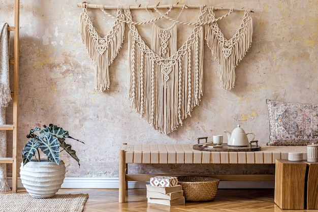 Дизайн интерьера стильной гостиной с бежевым шезлонгом, красивым макраме, деревянным кубом, лестницей, растениями, чайником на подносе и элегантными личными аксессуарами. восточная концепция домашнего декора.