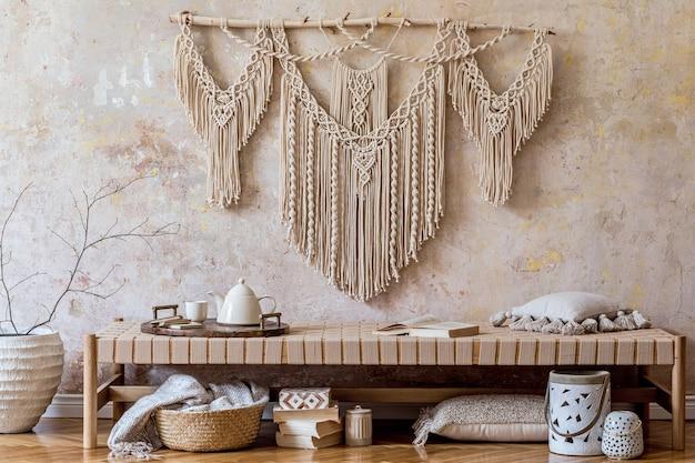 Дизайн интерьера стильной гостиной с бежевым шезлонгом, подушками, фонарем, макраме, засушенным цветком, чайником на подносе, декором и элегантными личными аксессуарами в восточной концепции.