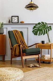 빈티지 녹색 안락 의자, 커피 테이블, 가구, 회색 벽, 선반, 카펫, 식물, 꽃병에 잎, 푸프, 펜던트 램프 및 우아한 개인 액세서리가있는 세련된 거실의 인테리어 디자인.