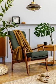 ヴィンテージグリーンのアームチェア、コーヒーテーブル、家具、灰色の壁、棚、カーペット、植物、花瓶の葉、プーフ、ペンダントランプ、エレガントなパーソナルアクセサリーを備えたスタイリッシュなリビングルームのインテリアデザイン。