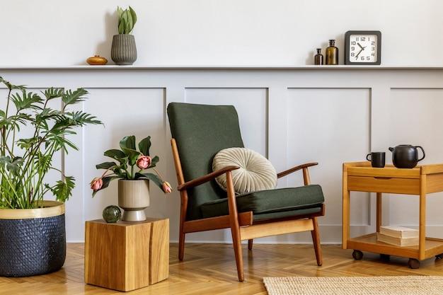 Дизайн интерьера стильной гостиной с винтажным зеленым креслом, деревянным журнальным столиком, мебелью, серой стеной, полкой, ковром, растениями, листьями в вазе, книгой, местом для копирования и элегантными личными аксессуарами.