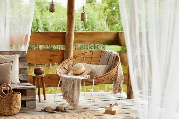 湖畔の夏の望楼のインテリアデザイン。スタイリッシュな籐のアームチェア、コーヒーテーブル、ソファ、枕、格子縞、エレガントなアクセサリーがモダンなインテリアで飾られています。夏の雰囲気。冷静になる。テンプレート。