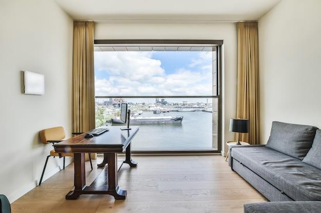 モダンで豪華なアパートの船と運河の景色を望む部屋のテーブルと灰色の柔らかいソファの上のコンピューターと職場のインテリアデザイン