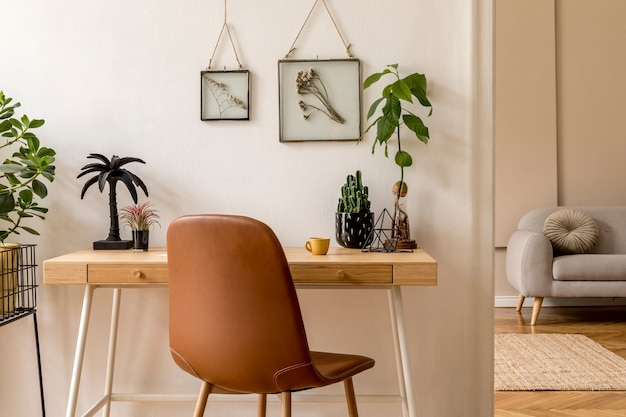 Interior design of scandinavian open space with photo frames, wooden desk, gray sofa, cacti, books office and personal accessories. stylish neutral home staging. beige walls..