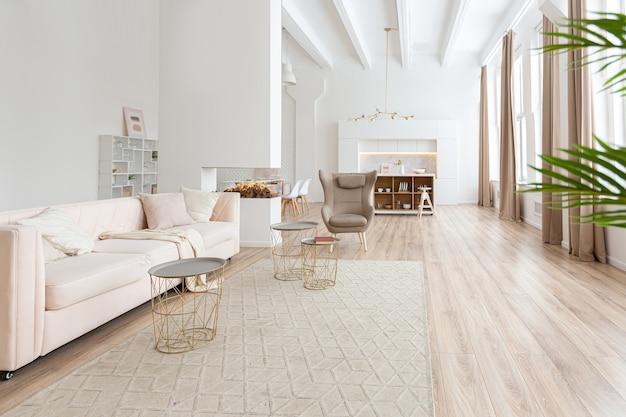 Дизайн интерьера просторной светлой квартиры выполнен в скандинавском стиле в теплых пастельных бело-бежевых тонах. модная мебель в гостиной и современные детали в кухонной зоне.