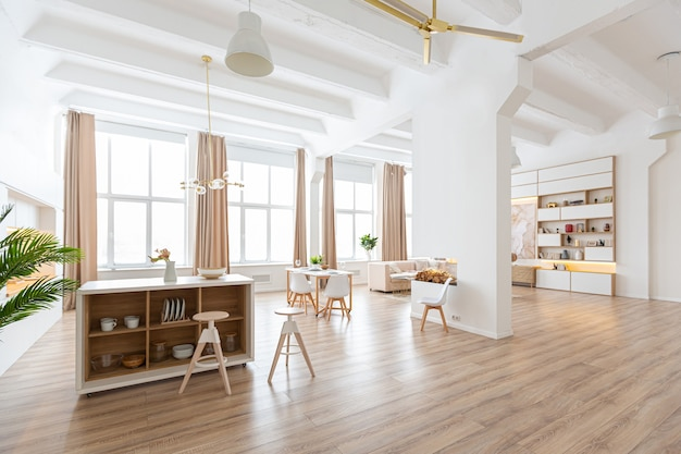 Interior design spacious bright apartment in scandinavian style and warm pastel white and beige colors. trendy furniture in the living area and modern details in the kitchen area.