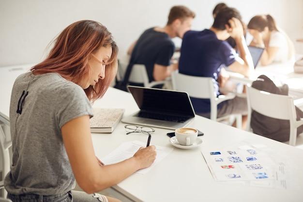 배경에 사람들과 캠퍼스 또는 밝은 코 워킹 스튜디오에서 작업하는 양식을 작성하는 인테리어 디자인 학생. 교육 개념.
