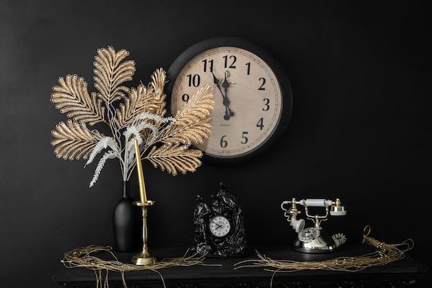 花とキャンドルの時計と暖炉の棚に古いレトロなヴィンテージの電話とインテリアデザインの花瓶。古いレトロなスタイルのヴィンテージインテリアイメージ