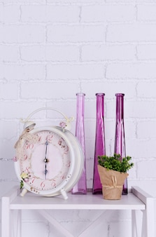 Interior design with alarm clock, plant and decorative vases on tabletop on white brick wall
