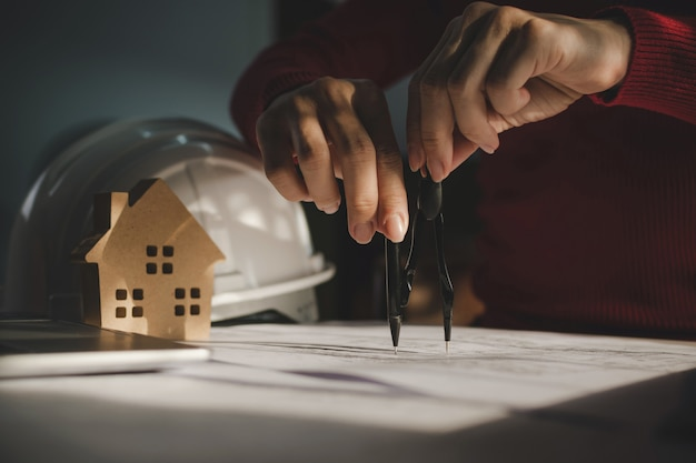 Interior designer drawing on blueprint with house model