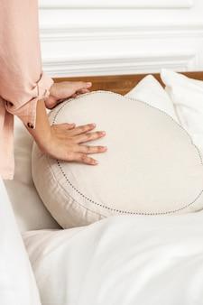 Interior designer che posiziona un cuscino rotondo su un letto