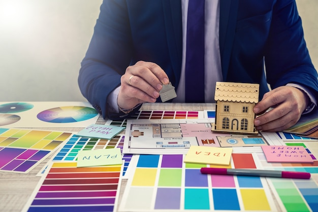 Interior designer's hand working with illustration sketch, color scheme of material, notebook and material. concept of home renovation, repair  or decoration