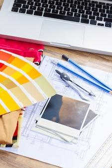 Рабочий стол дизайнера интерьера, архитектурный план дома, справочник цветовой палитры и образцы тканей в желтых тонах, копирование места на мгновенных пустых фотографиях
