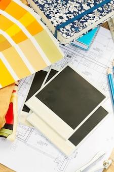 Рабочий стол дизайнера интерьера, архитектурный план дома, цветовая палитра и образцы тканей в желтых тонах, копирование места на мгновенных пустых фотографиях