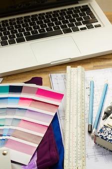 家の建築計画、キー、カラーパレットガイド、ラップトップを備えたインテリアデザイナーの作業デスクトップ