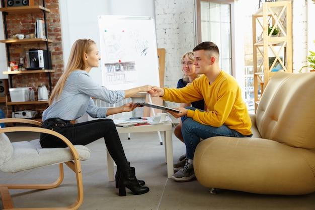 젊은 부부와 함께 작업하는 인테리어 디자이너. 사랑스러운 가족 및 전문 디자이너 또는 건축가가 미래의 인테리어 개념을 논의하고 색상 팔레트, 현대 사무실의 방 도면 작업.