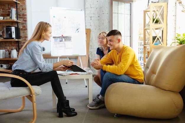 若いカップルと一緒に働くインテリアデザイナー。素敵な家族とプロのデザイナーまたは建築家が将来のインテリアの概念について話し合い、カラーパレット、現代のオフィスの部屋の図面を扱います。