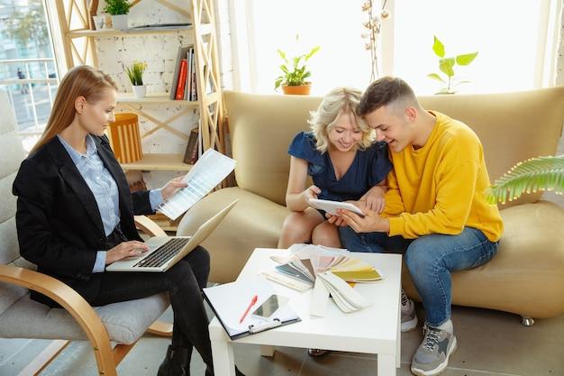 Interior designer che lavora con una giovane coppia. bella famiglia e designer professionista o architetto che discute del concetto di interni futuri, lavorando con tavolozza dei colori, disegni di stanze in un ufficio moderno
