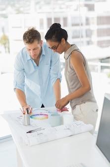 カラーホイールと青写真を見ているインテリアデザイナー