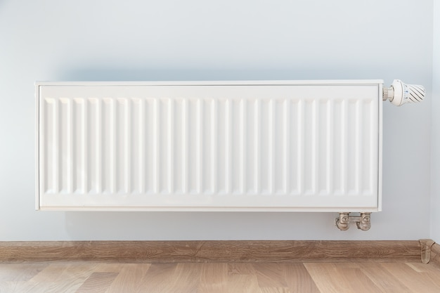 Interior detail. white metal radiator on white wall