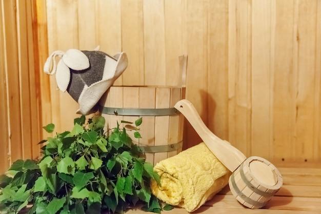 Детали интерьера финская сауна парилка с традиционными принадлежностями для сауны бассейн березовый веник совок фетровая шапка полотенце. традиционная старая русская баня spa concept. расслабляющая концепция деревенской бани