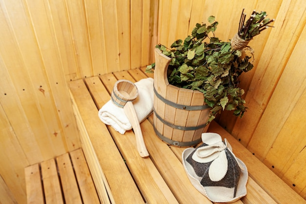 Interior details finnish sauna steam room with traditional sauna accessories basin birch broom scoop felt hat towel