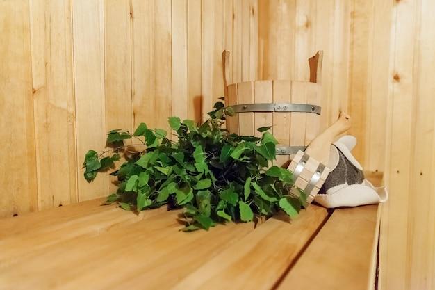 Детали интерьера финская сауна парная с традиционными сауными принадлежностями бассейн березовый веник совок фетровая шляпа. традиционная старая русская баня spa concept. расслабляющая концепция деревенской бани