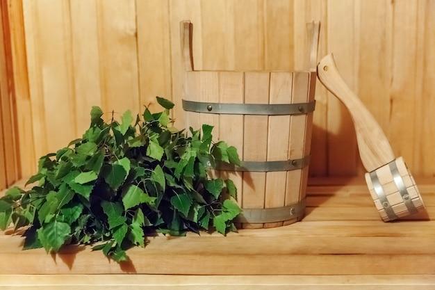 Детали интерьера финская сауна паровая баня с традиционными сауными принадлежностями бассейн березовый веник совок. традиционная старая русская баня spa concept. расслабляющая концепция деревенской бани