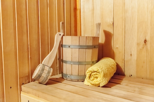 Interior details finnish sauna steam room with traditional sauna accessories basin scoop towel. traditional old russian bathhouse spa concept. relax country village bath concept