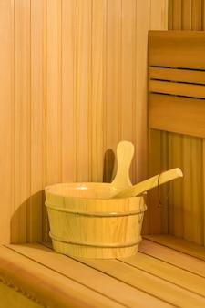 Детали интерьера финская баня-парилка с традиционными банными принадлежностями, совок для бассейна.