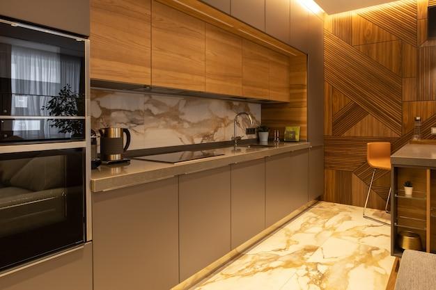 인테리어 디테일. 현대 아파트의 주방. 천연 재료. 가전제품, 주전자, 커피머신, 빌트인 오븐, 전자레인지. 바 카운터, 높은 의자. 벽에 디자이너 나무 패널입니다.