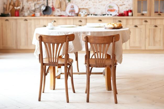 椅子が付いている丸い素朴なダイニングテーブルが付いている内部の食堂。