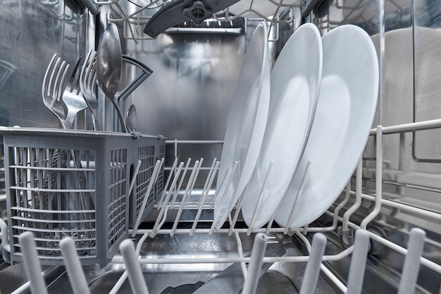 Interior of dishwasher machine with clean dishes after washing.