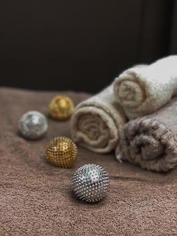 뷰티 스튜디오의 편안함을 위한 인테리어 요소입니다. 마사지 룸의 쾌적한 분위기. 스파 배경입니다. 아름답게 접힌 수건, 금색과 은색 마사지 볼