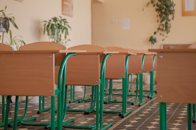 Interior of empty classroom with chairs and desks in a row