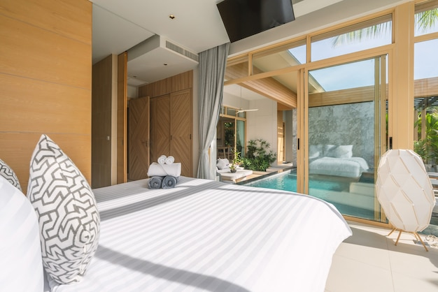 Interior and exterior design in bedroom of luxury pool villa, house, home feature swimming pool