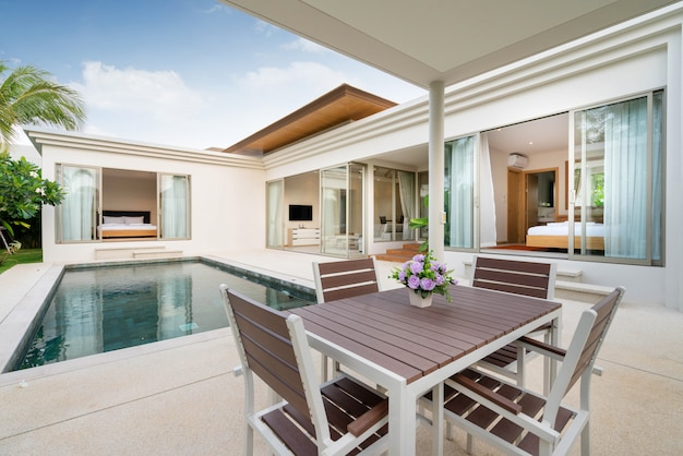 Interior and exterior design of outdoor dining table by pool terrace of villa, house and home