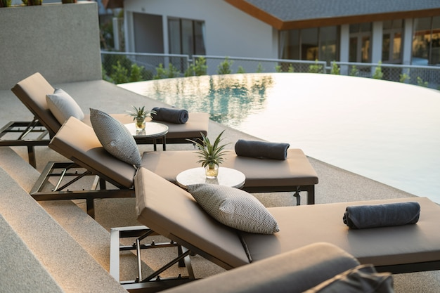 Interior and exterior design of pool villa, house and home feature sun bed and cushion by pool terrace