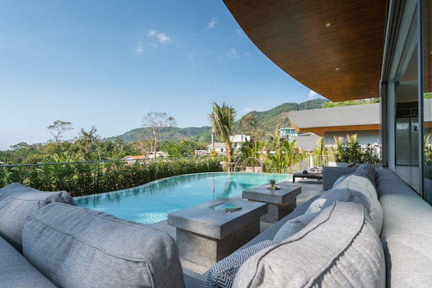 Interior and exterior design of pool villa, house, and home feature sun bed and infinity swimming pool